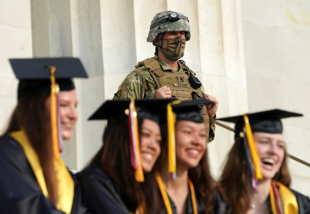A soldier keeps watch for activity following the death in Minneapolis police custody of George Floyd as graduates from Virginia's James Madison High School pose for photos at the Lincoln Memorial in Washington, U.S., June 5, 2020. (Photo by Kevin Lamarque/Reuters)
