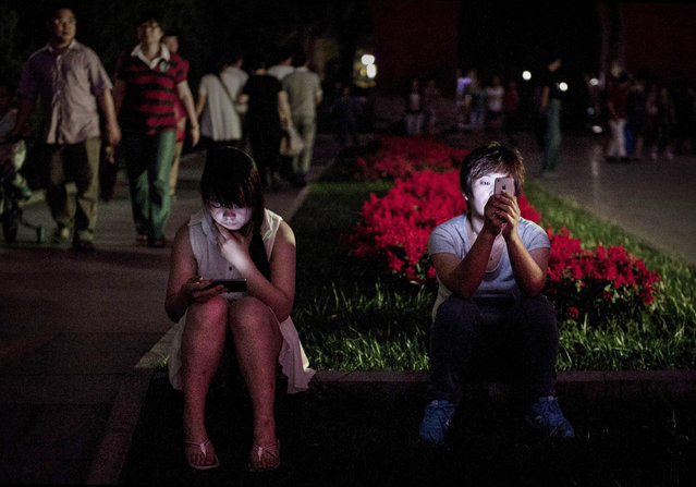 Chinese women use their smartphones in a park on September 10, 2014 in Beijing, China. China tightened censorship on mobile messaging apps last month and blocked a number of foreign chat services, according to media reports. (Photo by Kevin Frayer/Getty Images)