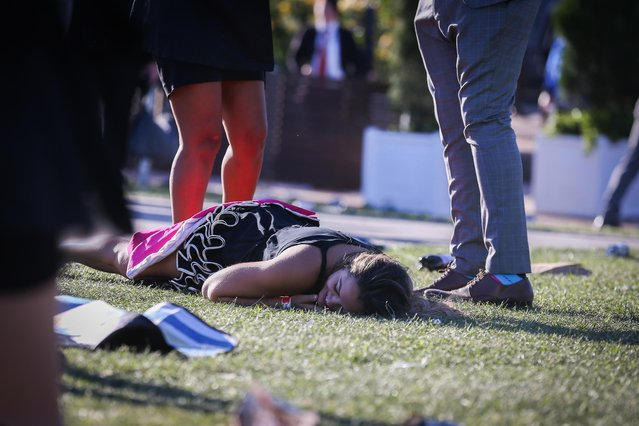 A woman lies face-down on the floor where other race-goers are standing on 2017 Derby Day at Flemington Racecourse on November 4, 2017 in Melbourne, Australia. (Photo by Splash News and Pictures)