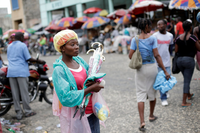 A street vendor selling umbrellas and raincoats awaits for customers along a street in Port-au-Prince, Haiti, August 1, 2016. (Photo by Andres Martinez Casares/Reuters)