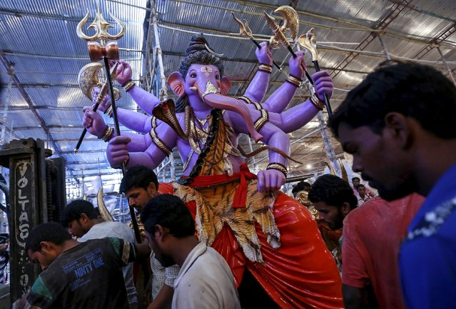 Workers carry an idol of Hindu elephant god Ganesh, the deity of prosperity, as it is transported from a workshop to a place of worship in Mumbai, India, September 9, 2015. Work on Ganesh idols usually begins two to three months before Ganesh Chaturthi, a popular religious festival in India that will be held in September this year. (Photo by Danish Siddiqui/Reuters)