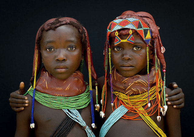 """Two Mumuhuilas little girls – Angola. Those little girls from the Mumuhuila tribe live near Chibia, in the south of Angola. They wear the traditional hairstyle and the big necklace. The necklace shows if they are teens or not. They still are children as the necklace is red. On their hair, they wear the traditional hairstyle, made with a mix of trunk, oil and cow dung. It was impossible to make them smile as pausing for a white man was too impressive for them, it was the first time they met tourist. Imagine the face they had when i gave them a polaroid at the end of the session! Those little girls live dressed like that, they were not dressed for me"". (Eric Lafforgue)"