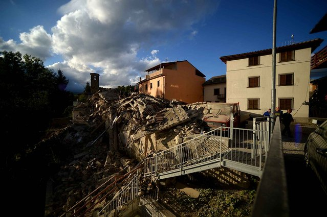 Residents walk past damaged buildings after a strong heartquake hit Amatrice on August 24, 2016. Central Italy was struck by a powerful, 6.2-magnitude earthquake in the early hours, which has killed at least three people and devastated dozens of mountain villages. Numerous buildings had collapsed in communities close to the epicenter of the quake near the town of Norcia in the region of Umbria, witnesses told Italian media, with an increase in the death toll highly likely. (Photo by Filippo Monteforte/AFP Photo)