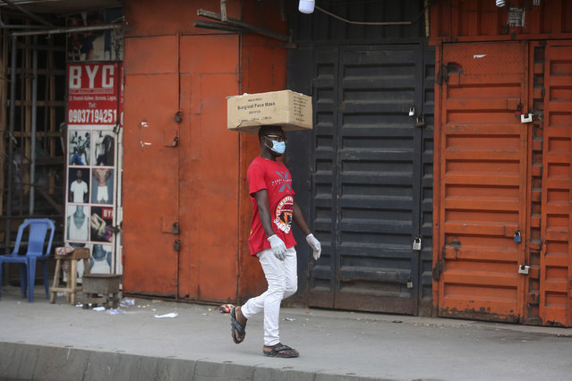 A man carries a box of surgical face masks on his head while wearing one, as he walks past closed shops due to a government ban on the operation of non-essential businesses and markets to halt the spread of the new coronavirus, in Lagos, Nigeria Thursday, March 26, 2020. (Photo by Sunday Alamba/AP Photo)