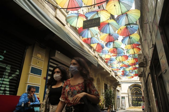 People, wearing protective masks against the spread of coronavirus, walk on a market area off Istiklal street, the main shopping street in Istanbul, Thursday, June 18, 2020. (Photo by Emrah Gurel/AP Photo)