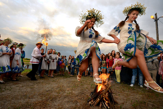 Girls wearing traditional costumes and flower wreaths jump over a bonfire during festivities marking Ivan Kupala Day, a pagan summer solstice celebration, in the town of Turov, Belarus on July 7, 2016. (Photo by Viktor Drachev/TASS)