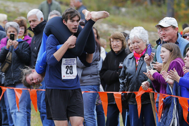 Brian Chin carries Kerrie Keller while competing in the North American Wife Carrying Championship at Sunday River ski resort in Newry, Maine October 11, 2014. REUTERS/Brian Snyder