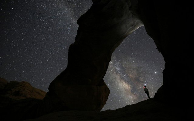A man watches the stars seen on the sky of Al-Kharza area of Wadi Rum in the south of Amman, Jordan, July 27, 2019. (Photo by Muhammad Hamed/Reuters)