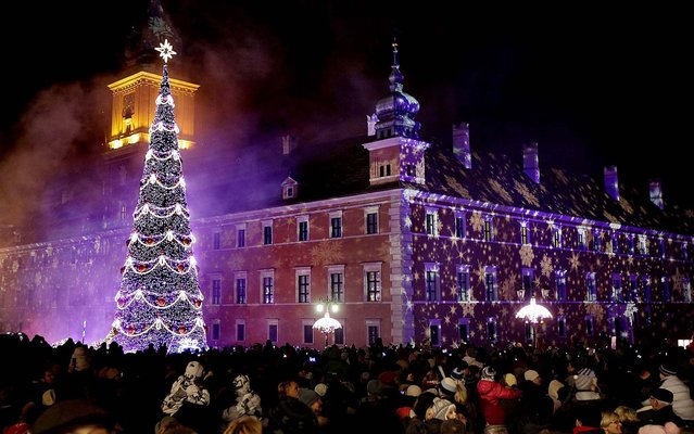 People enjoy Christmas illuminations on Royal Treaty Street in Warsaw, Poland. (Photo by Czarek Sokolowski/Associated Press)