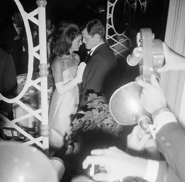 Jacqueline Kennedy confers with her brother-in-law Sen. Edward M. Kennedy during the $1,000-a-box benefit last night, on September 25, 1965 in Symphony Hall at Boston. It was the young widow's first social appearance in the home city of her husband, former Pres. John F. Kennedy, since his death 22 months ago. The ball celebrated the 85th birthday of the Boston Symphony Orchestra. (Photo by Frank Curtin/AP Photo)