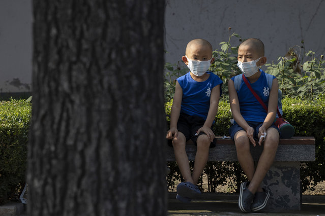 Children wearing masks to curb the spread of the coronavirus sit on a bench in Beijing, China on Monday, July 13, 2020. China reported only a handful of new cases of the virus, all of them brought from outside the country, as domestic community infections fall to near zero. (Photo by Ng Han Guan/AP Photo)