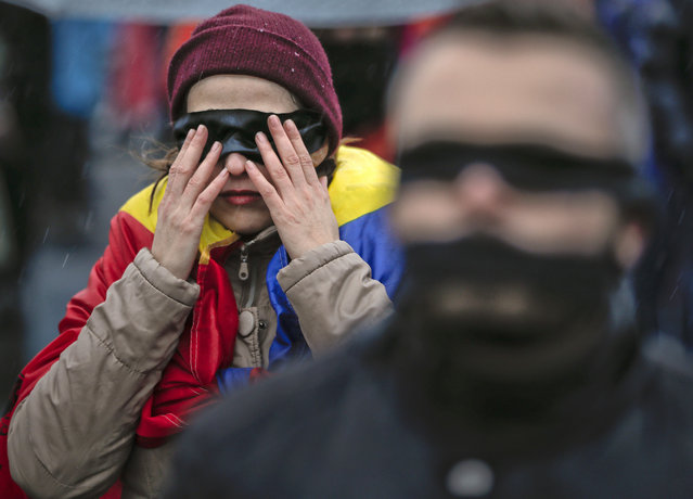People stand during a flash mob in Bucharest, Romania, Sunday, December 17, 2017. Protesters braved low temperatures and rain covering their mouths and eyes with black ribbons during a flash mob outside the government headquarters against planned modifications to Romanian justice legislation that critics say would render it less effective in punishing high-level corruption. (Photo by Vadim Ghirda/AP Photo)