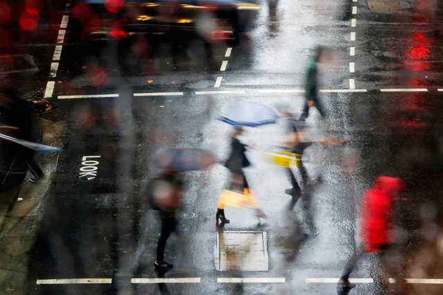 People are seen in Sydney's CBD as rain falls on January 17, 2020 in Sydney, Australia. A severe thunderstorm warning has been issued for some parts of Sydney as the city experiences its wettest day in four months. The rain is welcome relief after months of bushfires which have been burning across NSW. (Photo by Jenny Evans/Getty Images)
