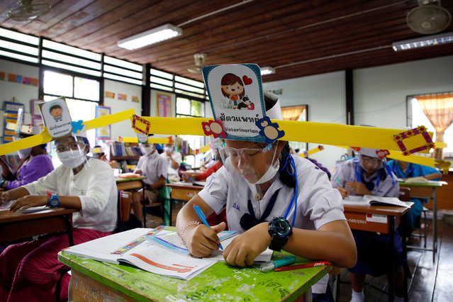 Students wearing face masks and one-meter social distancing wing-hats take part in a class at Ban Pa Muad School in San Sai district, Chiang Mai province, Thailand, 03 July 2020. Ban Pa Muad School, in northern Thailand, has created wing-hats, inspired by an ancient Chinese hat worn by the emperor and officials of the Song dynasty. The wing-hat was employed to ensure one meter in distance for children at the school. (Photo by Pongmanat Tasiri/EPA/EFE)