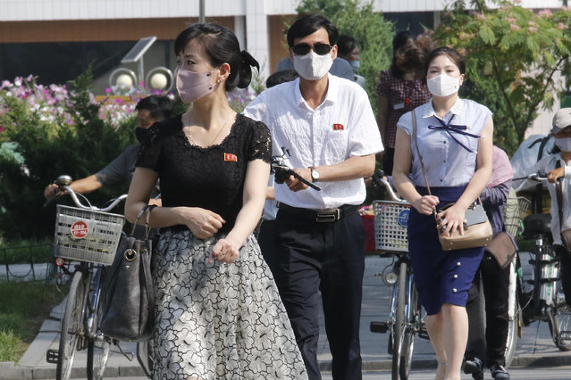 """People wearing masks walk in the Ryomyong street in Pyongyang, North Korea Friday, July 3, 2020. North Korean leader Kim Jong Un urged officials to maintain alertness against the coronavirus, warning that complacency risked """"unimaginable and irretrievable crisis,"""" state media said Friday. (Photo by Jon Chol Jin/AP Photo)"""