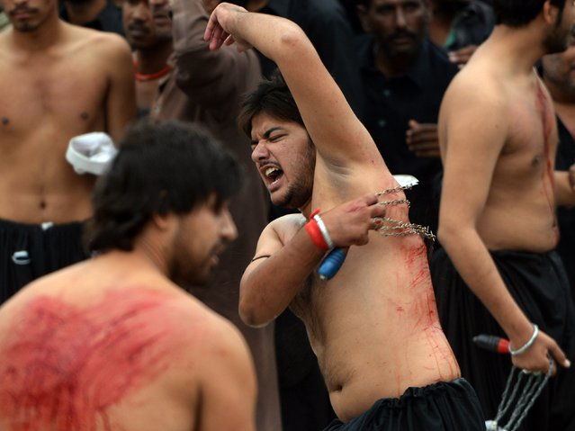 Pakistani Shiite Muslims flagellate themselves during a religious procession on the ninth day of holy Islamic month of Moharram in Islamabad on November 3, 2014. Pakistan was on high alert for the mourning processions of Ashura, a flashpoint for sectarian violence, a day after the country's deadliest bombing in more than a year killed 55 people. (Photo by Aamir Qureshi/AFP Photo)