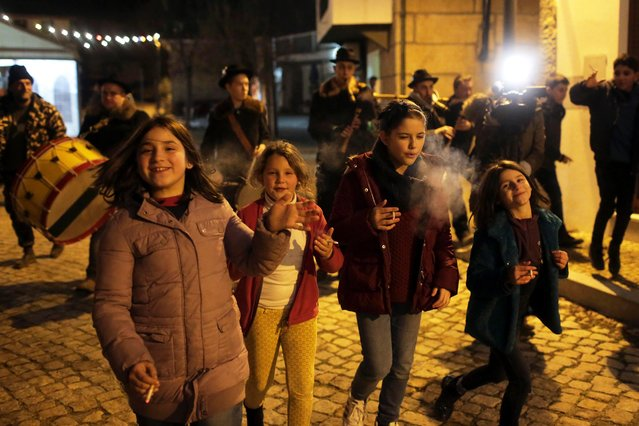 Children smoke while walking with a music band in the village of Vale de Salgueiro, northern Portugal, during the local Kings' Feast Friday night, January 5, 2018. The village's Epiphany celebrations, called Kings' Feast, feature a tradition that each year causes an outcry among outsiders: parents encourage their children, some as young as 5, to smoke cigarettes. The local tradition dictates that children as young as five are permitted to smoke on the special occasion, despite the legal buying age for tobacco being 18 in Portugal. Every year the event, called the King's Feast, draws outrage and strong criticism from outsiders. But despite the annual backlash, parents have continued to honour the allegedly centuries-old tradition by purchasing packets of cigarettes for their kids. The practice is technically legal in the country as nothing in the law prohibits parents giving children cigarettes and authorities do not intervene to stop them. (Photo by Armando Franca/AP Photo)