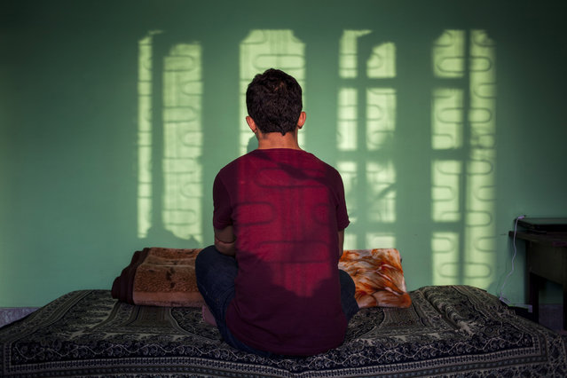 In this Sunday, September 14, 2014 photo, a 27-year-old Tibetan boy, who did not want to disclose his identity, sits in his room in New Delhi, India. He escaped into India in 1992 and says the 22 years away from his family has made him strong and emotionless. His mother has grown old and conveys her yearning to meet him but he doubts whether he will get a visa. The Tibetan says he misses his parents when he watches family based dramas and movies. (Photo by Tsering Topgyal/AP Photo)