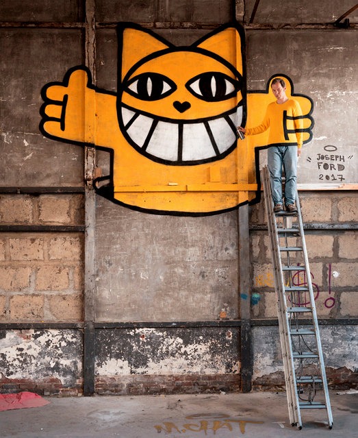 Here, a man stands on a ladder, camouflaging into the graffiti background. (Photo by Joseph Ford/South West News Service)