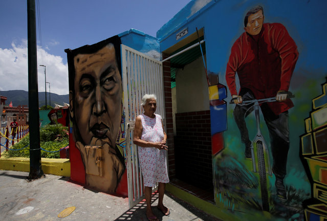 A resident stands next to a mural of Venezuela's late president Hugo Chavez outside her home in Caracas, Venezuela September 10, 2016. (Photo by Henry Romero/Reuters)