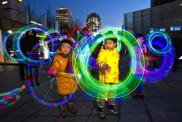 Children twirl colorful light-emitting toys in celebration of the upcoming first full moon of the lunar calendar in Seoul, South Korea, February 21, 2013. (Photo by Ahn Young-joon/Associated Press)