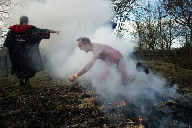 A competitor leaps over a fire as he participates in the Tough Guy endurance event near Wolverhampton, central England, on February 4, 2018. (Photo by Oli Scarff/AFP Photo)