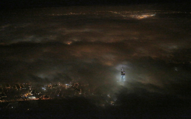 One World Trade Center emerges from the clouds in the night sky in a photo made from a passing airplane, Monday, March 12, 2013 in New York. Construction continues on the office complex going up on the site of the original World Trade Center that was destroyed in the terrorist attacks of September 11, 2001. (Photo by Matthew Ziegler/AP Photo)