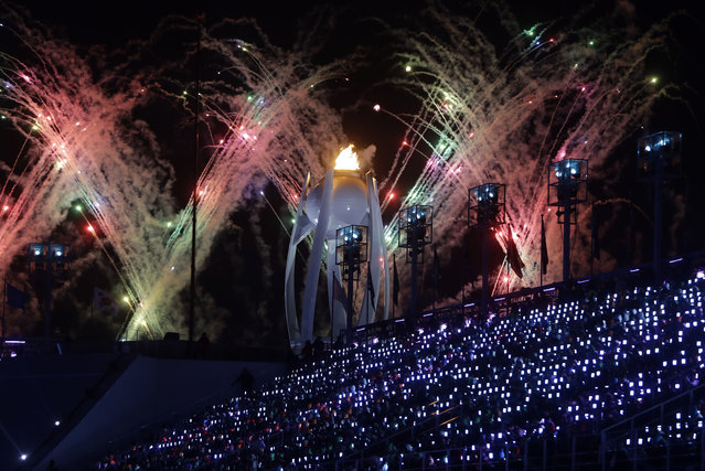Fireworks explode over the Olympic flame during the closing ceremony of the 2018 Winter Olympics in Pyeongchang, South Korea, Sunday, February 25, 2018. (Photo by Michael Probst/AP Photo)