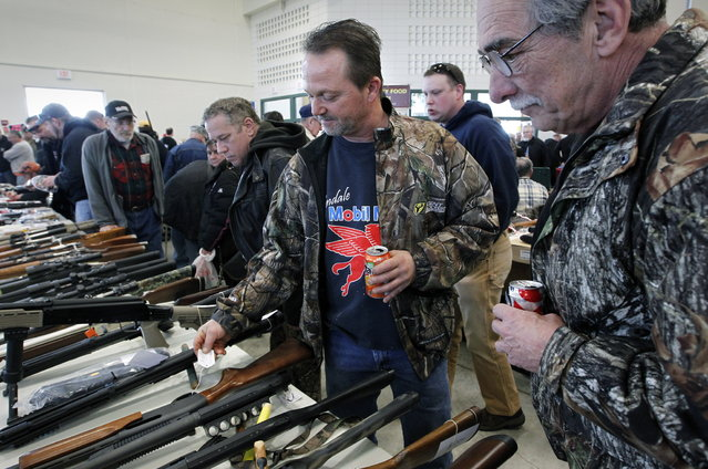 Rick Schaeffer, of Grafton, shops for a hunting rifle at the Washington County Fairgrounds Gun Show that drew thousands of people over the weekend, on March 22, 2013. (Photo by Gary Porter)