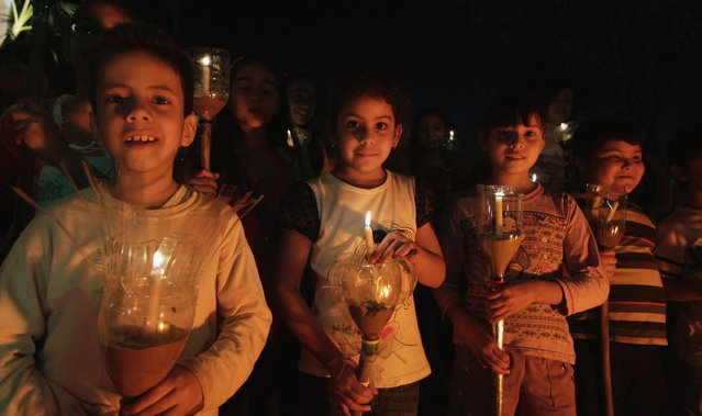 """Catholic children hold candles during the """"Via Crucis"""" (Way of the Cross) re-enactment in a procession during Holy Week, in preparation for Good Friday celebrations, in Luque March 27, 2013. Week is celebrated in many Christian traditions during the week before Easter. (Photo by Jorge Adorno/Reuters)"""