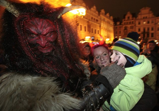 A reveller dressed as a devil strokes a child at the Old Town Square in Prague, on the eve of Saint Nicholas Day December 5, 2014. Revellers dressed as Saint Nicholas and a devil approached children on the streets as part of a tradition to determine if they had behaved well during the past year and depending on their answers, would receive presents, sweets or coal accordingly. (Photo by David W. Cerny/Reuters)