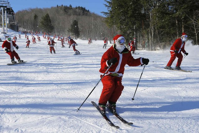 Skiers and snowboarders dressed as Santa Claus participate in a charity run down a slope at Sunday River Ski Resort in Newry, Maine December 7, 2014. (Photo by Brian Snyder/Reuters)