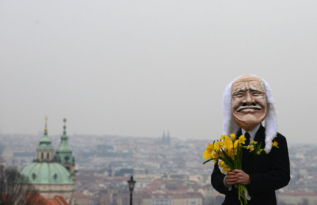 A man wearing a mask of Czech President Vaclav Klaus holds flowers during a march celebrating the end of his presidency, on March 7, 2013 at the Charles Bridge in Prague. (Photo by Michal Cizek/AFP Photo /The Atlantic)