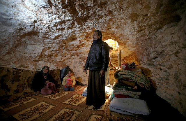 Sobhi al-Hamod, 60, lives with his family in an underground cave used for shelter from Syrian government forces in Idlib province, on February 28, 2013. (Photo by Hussein Malla/AP Photo /The Atlantic)