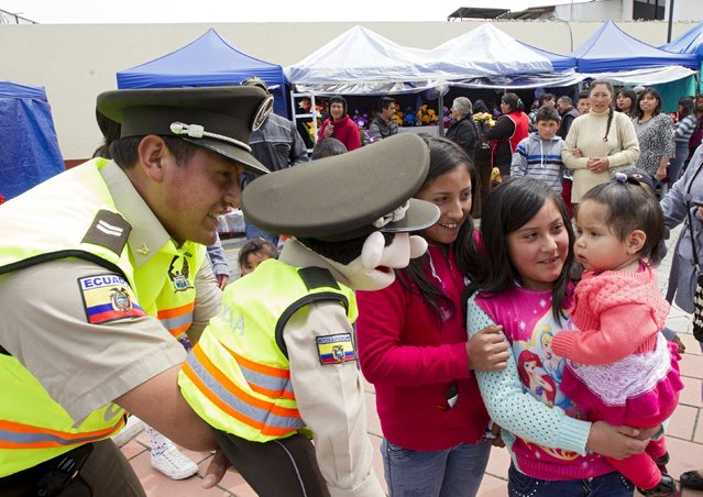 A police officer performs with a puppet for an educational campaign on children's rights, as youths and children watch, in Tulcan November 2, 2015. (Photo by Guillermo Granja/Reuters)