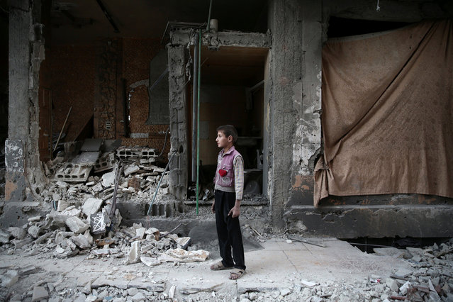 A boy stands near a damaged building after an airstrike yesterday in the rebel held Douma neighbourhood of Damascus, Syria October 4, 2016. (Photo by Bassam Khabieh/Reuters)
