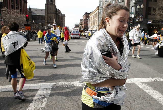 An unidentified Boston Marathon runner leaves the course crying near Copley Square following an explosion in Boston Monday, April 15, 2013. (Photo by Winslow Townson/AP Photo)
