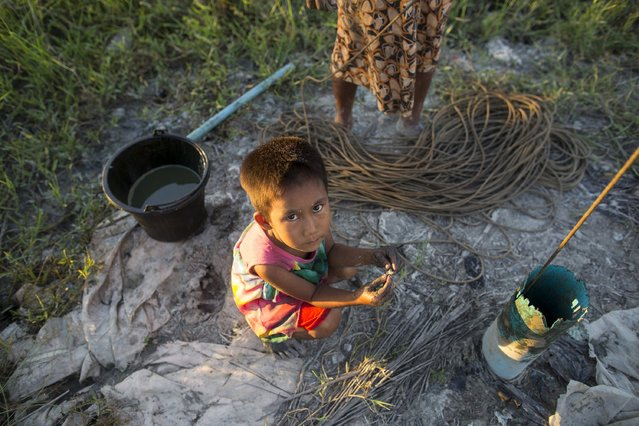 A child squats on the ground as her mother works to extract crude oil by hand on the seashore in Kyaukpyu township, Rakhine state, Myanmar October 5, 2015. (Photo by Soe Zeya Tun/Reuters)