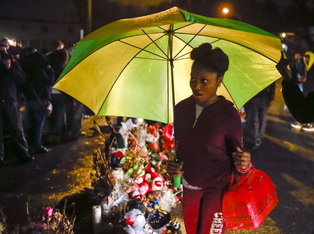 Ferguson resident Churnae Allred, 15, holds an umbrella to guard against the rain as she joins dozens who gathered to pay homage to Michael Brown at the site where he was shot and killed in Ferguson, Missouri November 22, 2014. (Photo by Adrees Latif/Reuters)
