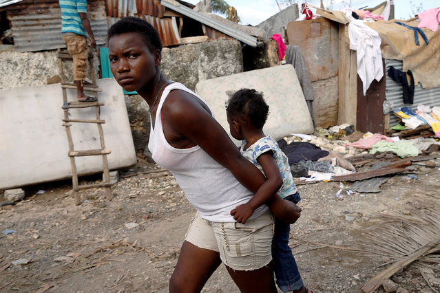 A woman carries a child as they walk in front of destroyed houses after Hurricane Matthew passes Jeremie, Haiti, October 7, 2016. (Photo by Carlos Garcia Rawlins/Reuters)