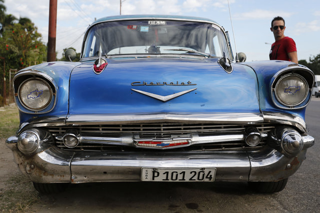 In this December 19, 2014 photo, a man stands beside his 1957 Chevrolet Bel-Air car in Havana, Cuba.  U.S. car sales have been banned in Cuba since 1959. Cubans have been have been forced to patch together Fords, Chevrolets and Chryslers that date back to before Fidel Castro's revolution which can make it appear like the country is stuck in a 1950s time warp. (Photo by Desmond Boylan/AP Photo)