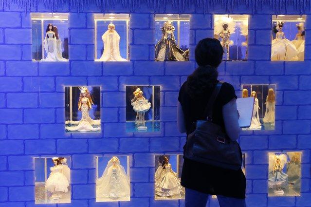 "A women watches  Mattel's Barbie dolls inside a ""Barbie Dreamhouse"" in Berlin, May 16, 2013. (Photo by Fabrizio Bensch/Reuters)"