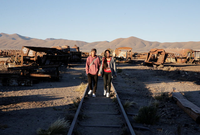 A couple walk among locomotives and wagons of Bolivian Railways Company from 1870-1900 at the train cemetery in Uyuni, Potosi, Bolivia on May 16, 2018. (Photo by David Mercado/Reuters)