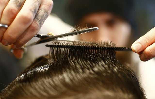 "Alex ""Torreto"" Vellios, a 26-year old Greek-born barber concentrates while styling the hair of a customer at his Torreto barber shop in Frankfurt January 6, 2015. (Photo by Kai Pfaffenbach/Reuters)"