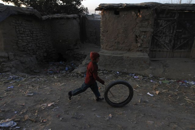 A boy plays with a tyre at a slum on the outskirts of Islamabad January 6, 2015. (Photo by Faisal Mahmood/Reuters)
