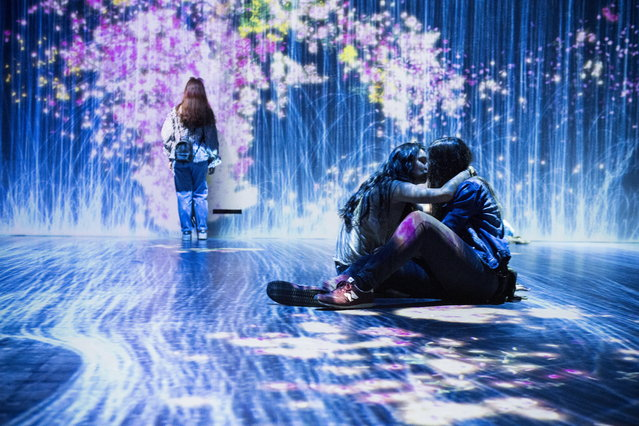 """People look at a digital artwork as part of the installation """"Au-delaa des limites"""" (Beyond limits) by Japanese group teamLab in Paris, France, 24 May 2018. The 2,000 square meter exhibition is on display until 09 September. (Photo by Julien De Rosa/EPA/EFE)"""