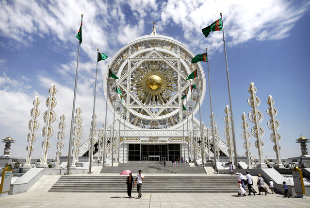 A young couple leave the Alem Entertainment Center in Ashgabat. The current president has a history of breaking obscure records. In 2012 the wheel atop this complex was entered into the Guinness Book of World Records as the world's largest enclosed Ferris wheel. The structure was built at a cost of $90m. (Photo by Amos Chapple via The Atlantic)