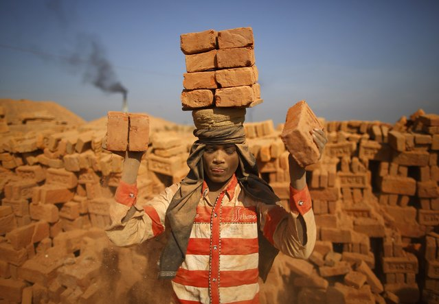 A worker stack bricks on his head at a brick factory in Lalitpur January 12, 2015. (Photo by Navesh Chitrakar/Reuters)
