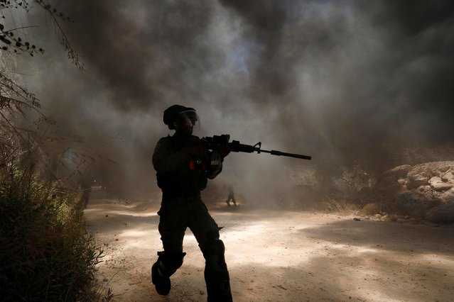 An Israeli border police member runs as smoke rises from burning tires during a Palestinian protest against Jewish settlements in the town of Beita in the Israeli-occupied West Bank on July 18, 2020. (Photo by Mohamad Torokman/Reuters)