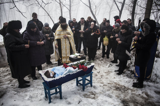 Mourners gather around a coffin bearing Artiam, 4, who was killed in a Ukrainian army artillery strike, during his funeral in Kuivisevsky district on the outskirts of Donetsk, eastern Ukraine, Tuesday, January 20, 2015. (Photo by Manu Brabo/AP Photo)